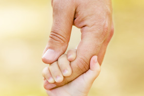 Child-holding-Adult-hand-295x196