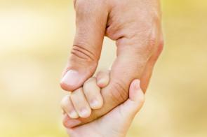 Child-holding-Adult-hand-295x196